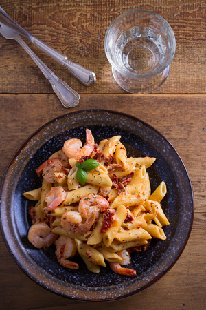 Shrimp penne with sun dried tomatoes and basil in creamy mozzarella sauce. Pasta with shrimps in bowl on wooden table. overhead, vertical