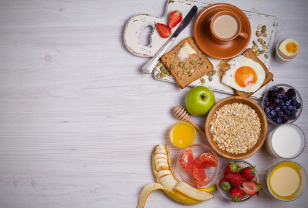 Breakfast served with coffee, orange juice, cereals, milk, fruits, eggs and toasts. Balance diet, food banner, background. View from above, top