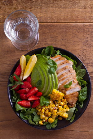 Strawberry, avocado, arugula, basil, sweet corn salad with chicken. Healthy diet food bowl. View from above, top studio shot