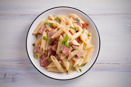 Penne pasta with bacon and sundried tomatoes. Alfredo penne pasta on white plate on wooden table. overhead, horizontal