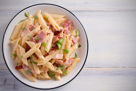 Penne pasta with bacon and sundried tomatoes. Alfredo penne pasta on white plate on wooden table. overhead, horizontal 写真素材 - 102027455