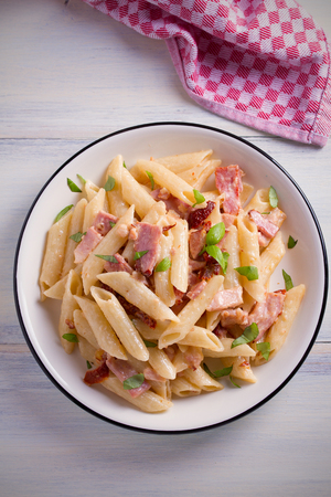Penne pasta with bacon and sundried tomatoes. Alfredo penne pasta on white plate on wooden table. overhead, vertical