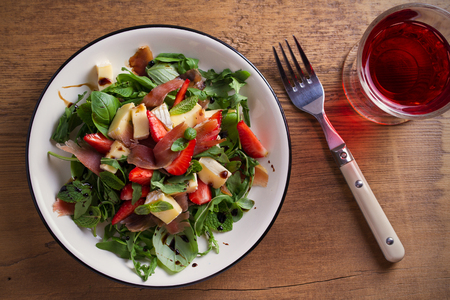 Strawberry, basil, mint, arugula salad with brie cheese and jamon on white plate on wooden table. horizontal, overhead Stock Photo