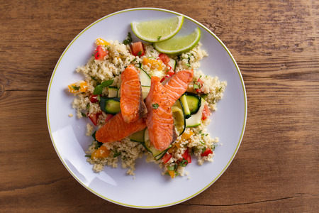 Salmon with tomato couscous, zucchini and lime. View from above, top studio shot Stock Photo