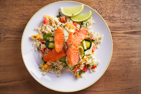 Roasted salmon fish with tomato couscous, zucchini and lime on white plate. overhead, horizontal