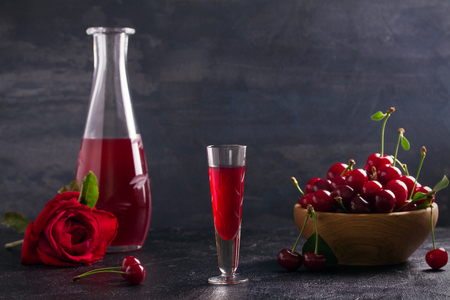 Homemade cherry alcohol drink liquor with fresh cherry berries. horizontal, room for text Standard-Bild
