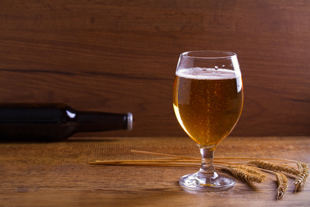 Glass and bottle of beer, ears of barley on wooden table. Ale. Room for text