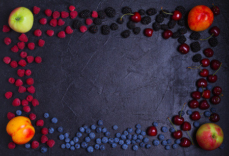 Various fresh summer berries. Mix of fruits and berries on black background. Fruit banner. Selection of healthy vegetarian food, detox or diet concept, space for text. Top view, overhead Banque d'images