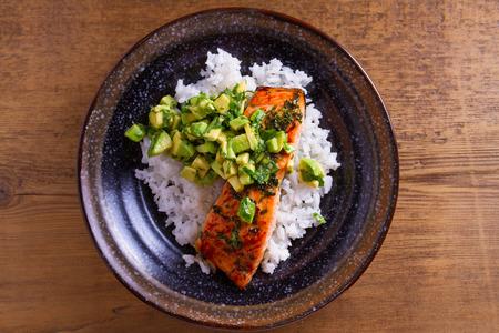Avocado salmon rice bowl. Salmon fillet roasted in honey, lime, cilantro glaze and fresh cilantro avocado. Fish steak. View from above, top studio shot Foto de archivo - 106663536