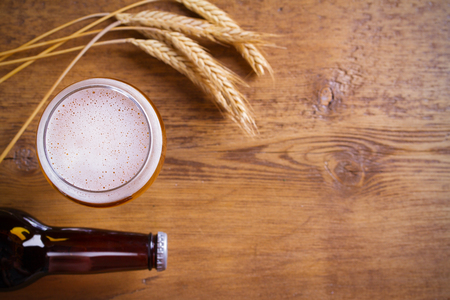 Glass and bottle of beer, ears of barley on wooden background. Ale. overhead, horizontal with copy space Stok Fotoğraf
