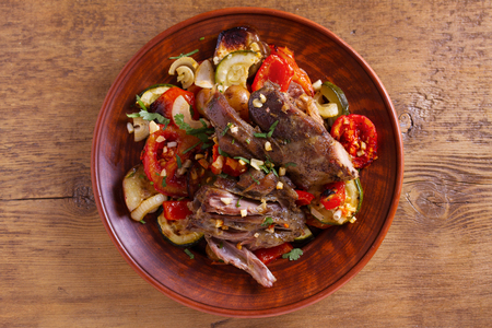 Slow cooker lamb with vegetables and garlic. View from above, top studio shot Stock Photo