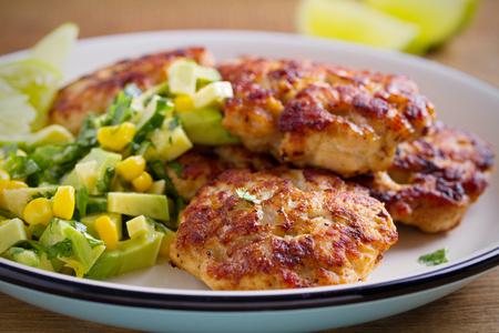 Homemade chicken patties or burgers with avocado corn salsa. horizontal