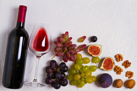 Glass and bottle of wine with grapes, figs and nuts on white stone texture background. View from above, top studio shot Archivio Fotografico