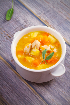 Chicken, butternut squash, apple, ginger and sage stew in white bowl on wooden table. Pumpkin soup with chicken. vertical