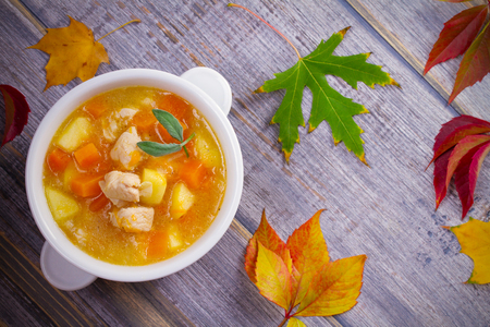 Chicken, butternut squash, apple, ginger and sage stew in white bowl on wooden table. Pumpkin soup with chicken. overhead, horizontal