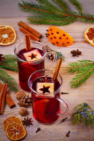 Mulled wine hot drink with spices, citrus fruits and apples. Seasonal and holidays concept
