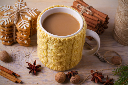 Knitted yellow cup with hot winter drink, cookies, cinnamon, decorations. Cozy