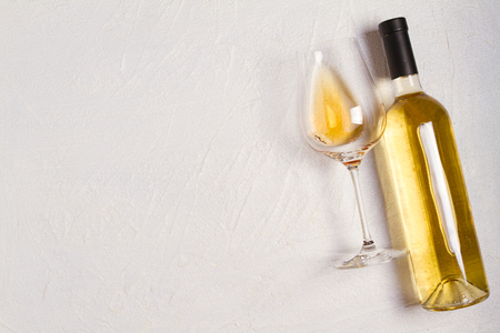 Glass and bottle of wine on white stone texture background. View from above, top studio shot
