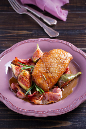 Duck breast with pancetta, rosemary and figs, baked in honey sauce. vertical Stock Photo