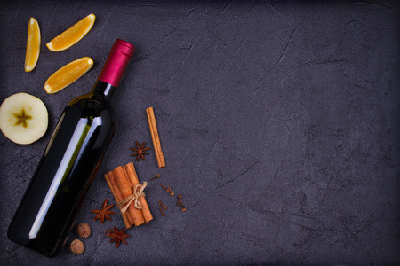 Bottle of red wine with spices, citrus fruits and apples for mulled wine hot drink. top view, horizontal Standard-Bild