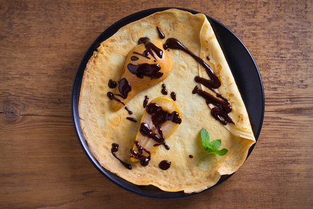 Crepes with baked pear and chocolate. Thin pancakes with baked pear and chocolate. overhead, horizontal