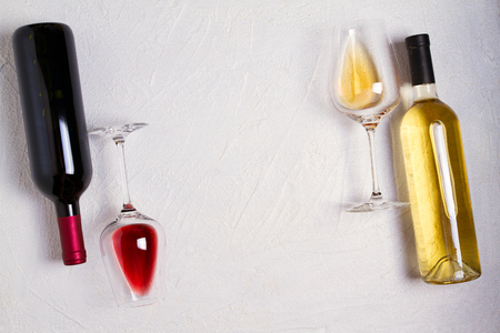 Glasses and bottles of red and white wine on white background. Wine still life. top view; horizontal Stock Photo