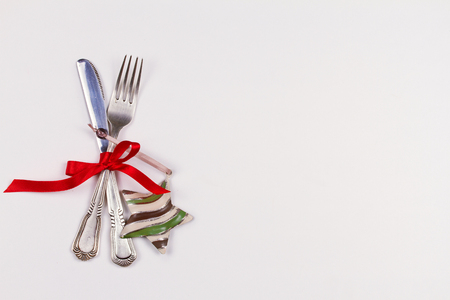 Christmas composition with cutlery, pine branch, ribbon and decorations on white table. Winter holidays and festive background. Christmas eve dinner, New Year food lunch.  top view