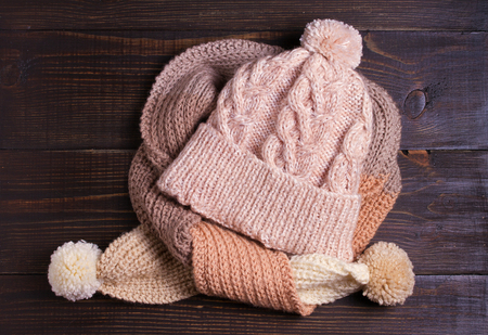 Knitted hat and scarf, winter concept. Women winter warm accessories on wooden background. Flat lay, view from above, top Banque d'images