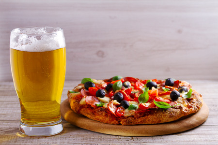 Glass of beer and pizza on wooden table. Beer and food concept. Ale. Copy space Stock Photo