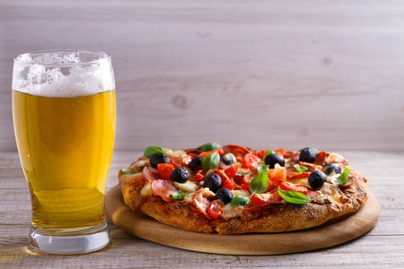 Beer and pizza on wooden plate. Ale and  snack. Horizontal