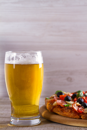 Beer and pizza on wooden plate. Ale and  snack. Vertical Stock Photo