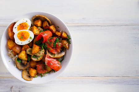 Smoked salmon breakfast bowl with egg, potatoes, mushrooms and rice. View from above, top studio shot