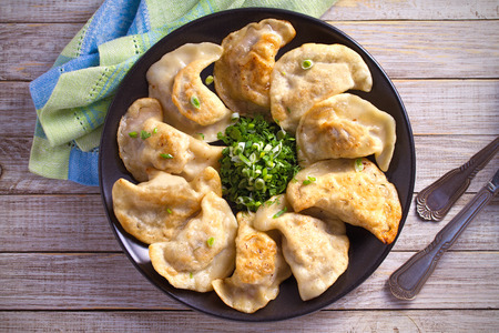 Fried dumplings stuffed with meat and served with chopped parsley and spring onion. overhead, horizontal