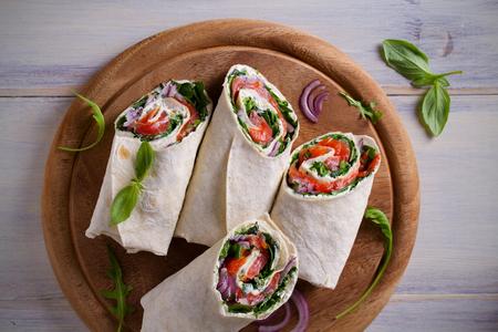 Smoked Salmon, Cream Cheese, Spinach and Arugula Wraps. Fish Burritos. overhead, horizontal