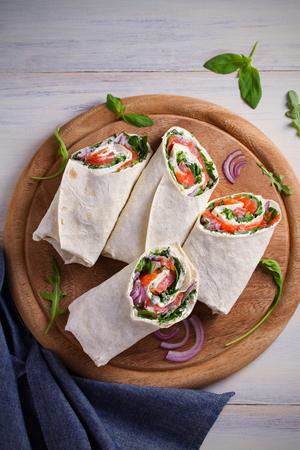 Smoked Salmon, Cream Cheese, Spinach and Arugula Wraps. Fish Burritos. overhead, vertical