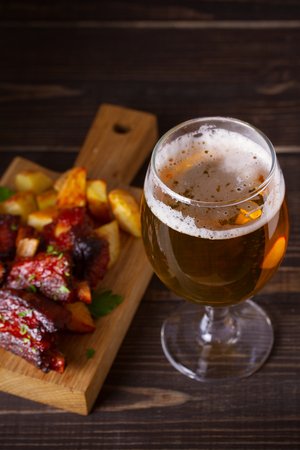Beer and pork spare ribs with fry. Beer and meat. Glass of ale. vertical Stock Photo