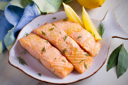 Cooked on steam salmon steaks with lemon. Dietary menu. White plate on white table. horizontal