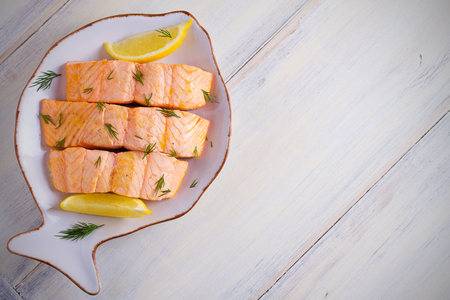 Cooked on steam salmon steaks with lemon. Dietary menu. White plate on white table. horizontal, overhead, copy space