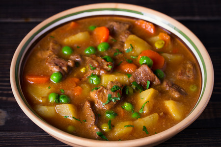 Homemade Irish beef stew with potatoes, carrots and peas in bowl on wooden table.  horizontal