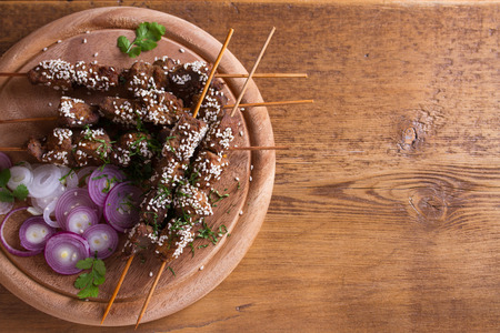 Beef liver on skewers with sesame seeds. Liver Kebab. View from above, top studio shot, copy space