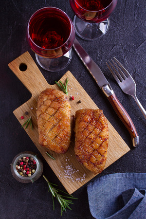 Duck breast, lavender honey and rosemary, served on chopping board, glasses of red wine. View from above, top studio shot