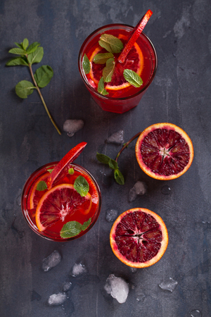 Blood orange cocktail with slices of citrus fruits and mint. View from above, top