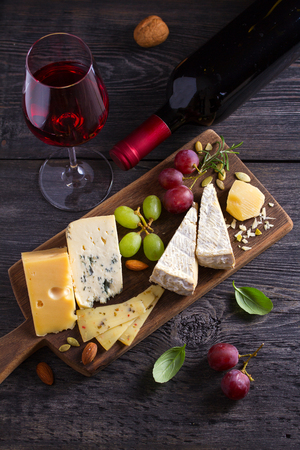 Glass and bottle of wine with cheese, grapes, and nuts on black wooden table. Wine and food. View from above, top studio shot Banque d'images - 122319053