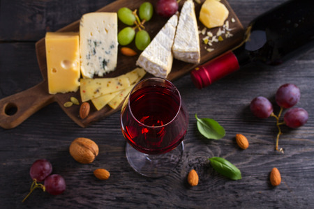 Glass and bottle of wine with cheese, grapes, and nuts on black wooden table. Wine and food. View from above, top studio shot Фото со стока