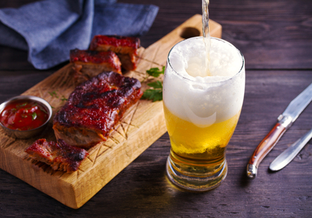 Beer and pork spare ribs. Beer and meat. Glass of ale