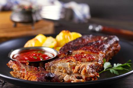 Żeberka wieprzowe z grilla z frytkami na czarnym talerzu. Pieczone pokrojone żeberka grillowe