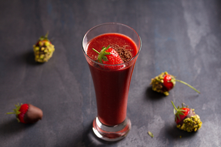 Chocolate strawberry smoothie and chocolate covered berries with chopped pistachios. Healthy drink