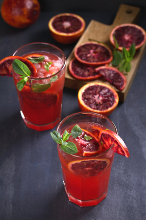 Two glasses of blood orange or red orange cocktail with slices of citrus fruits and mint - image