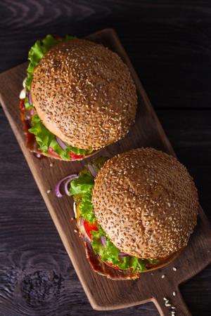 Two delicious homemade beef burgers with bacon on wooden chopping board. View from above, top studio shot Stock Photo