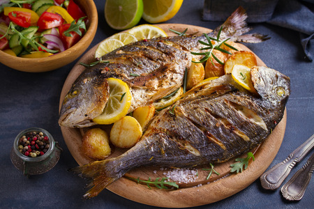 Roasted fish and potatoes, served on wooden tray - image